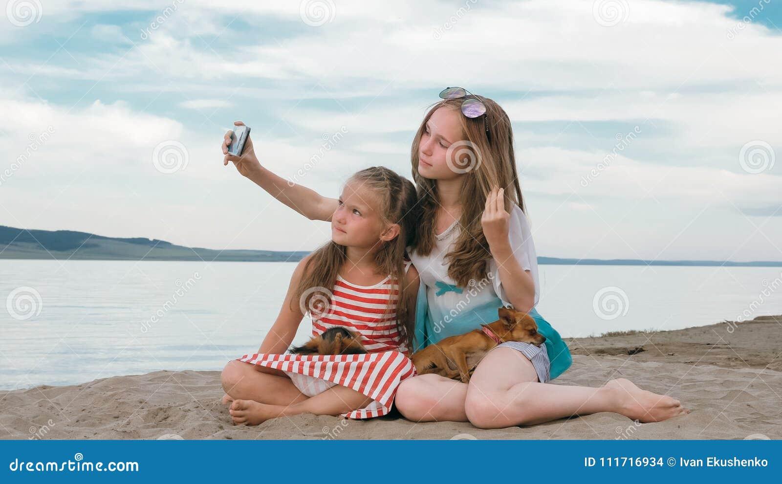 Dos adolescentes se están sentando en una playa arenosa, en Internet en teléfono