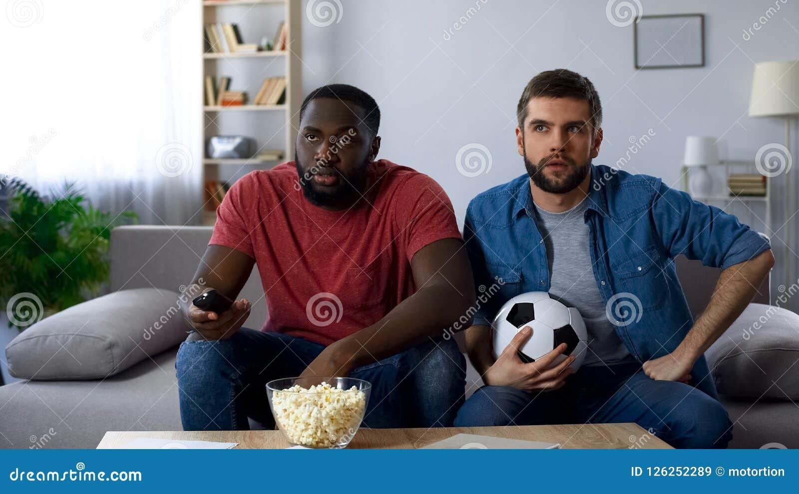 Dos aficionados al fútbol que miran fútbol americano hacen juego, intentando entender reglas