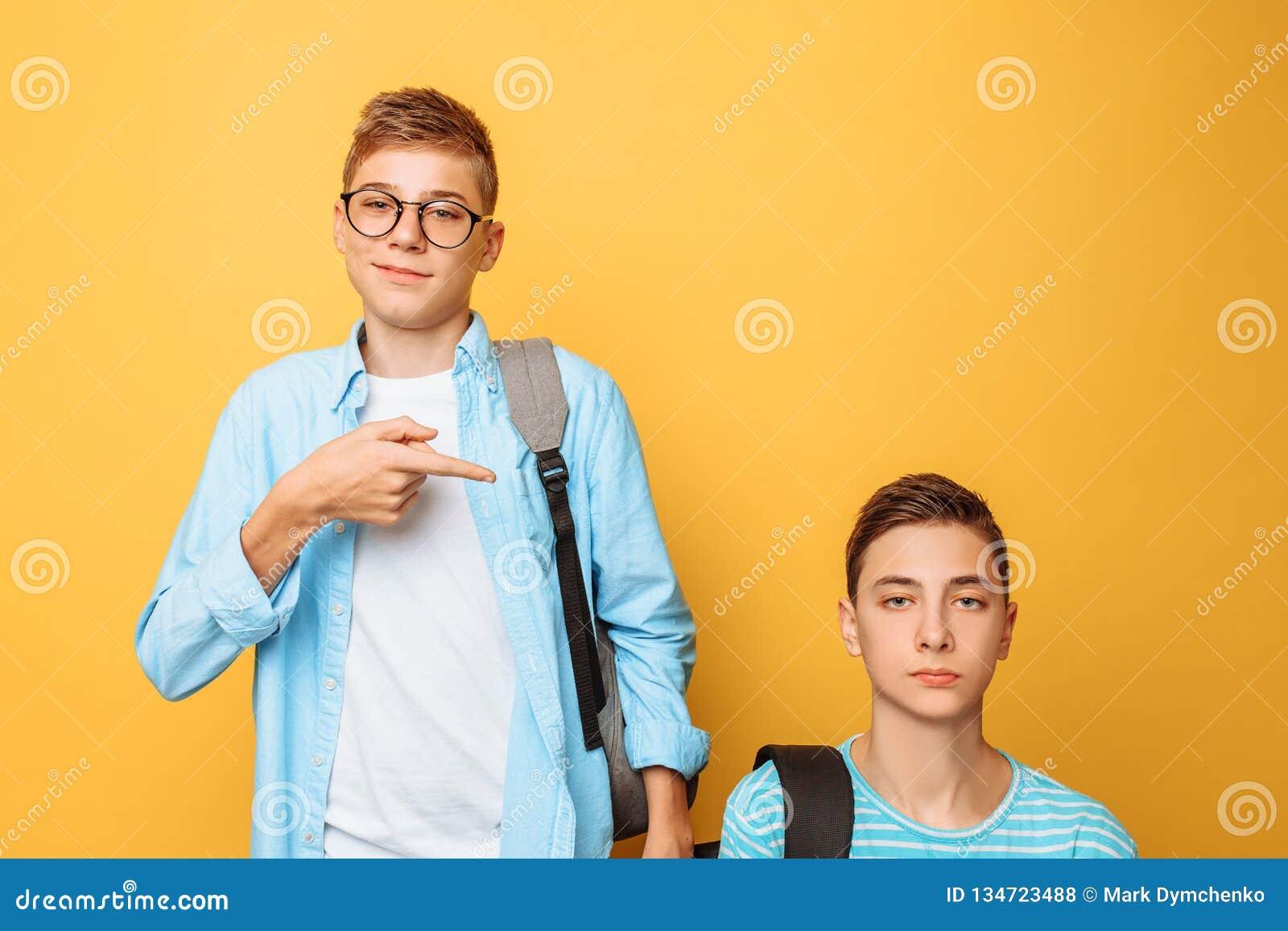Dos amigos adolescentes, un individuo humillan al otro, popular humillan el impopular, en un fondo amarillo