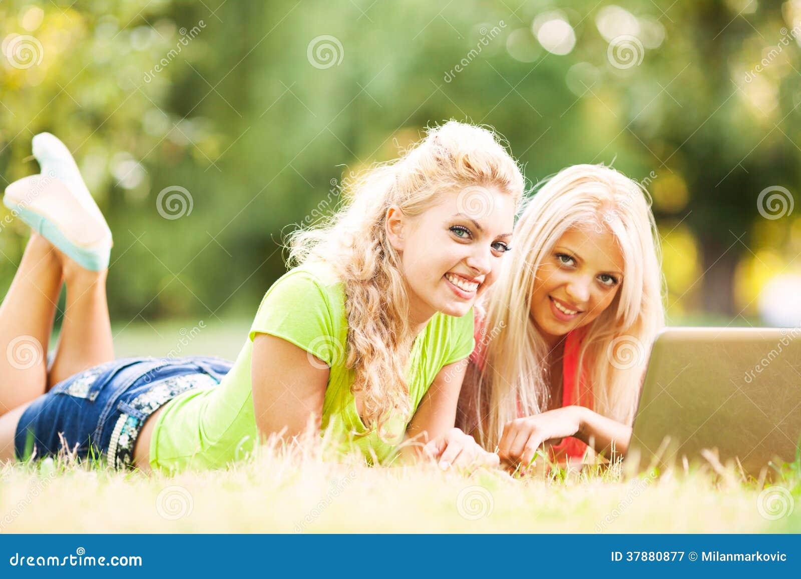 Dos amigos alegres con el ordenador portátil en el parque
