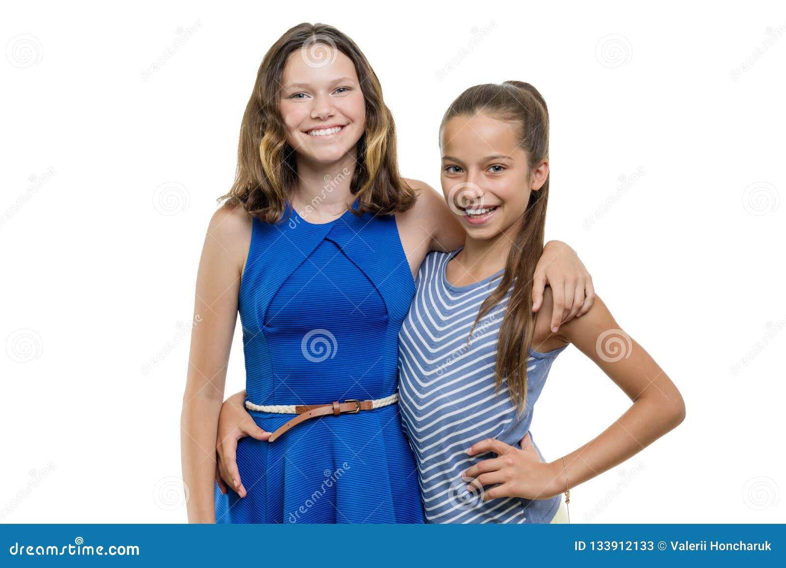 Dos amigos de chicas jóvenes hermosos felices que abrazan, con la sonrisa blanca perfecta, aislada en el fondo blanco