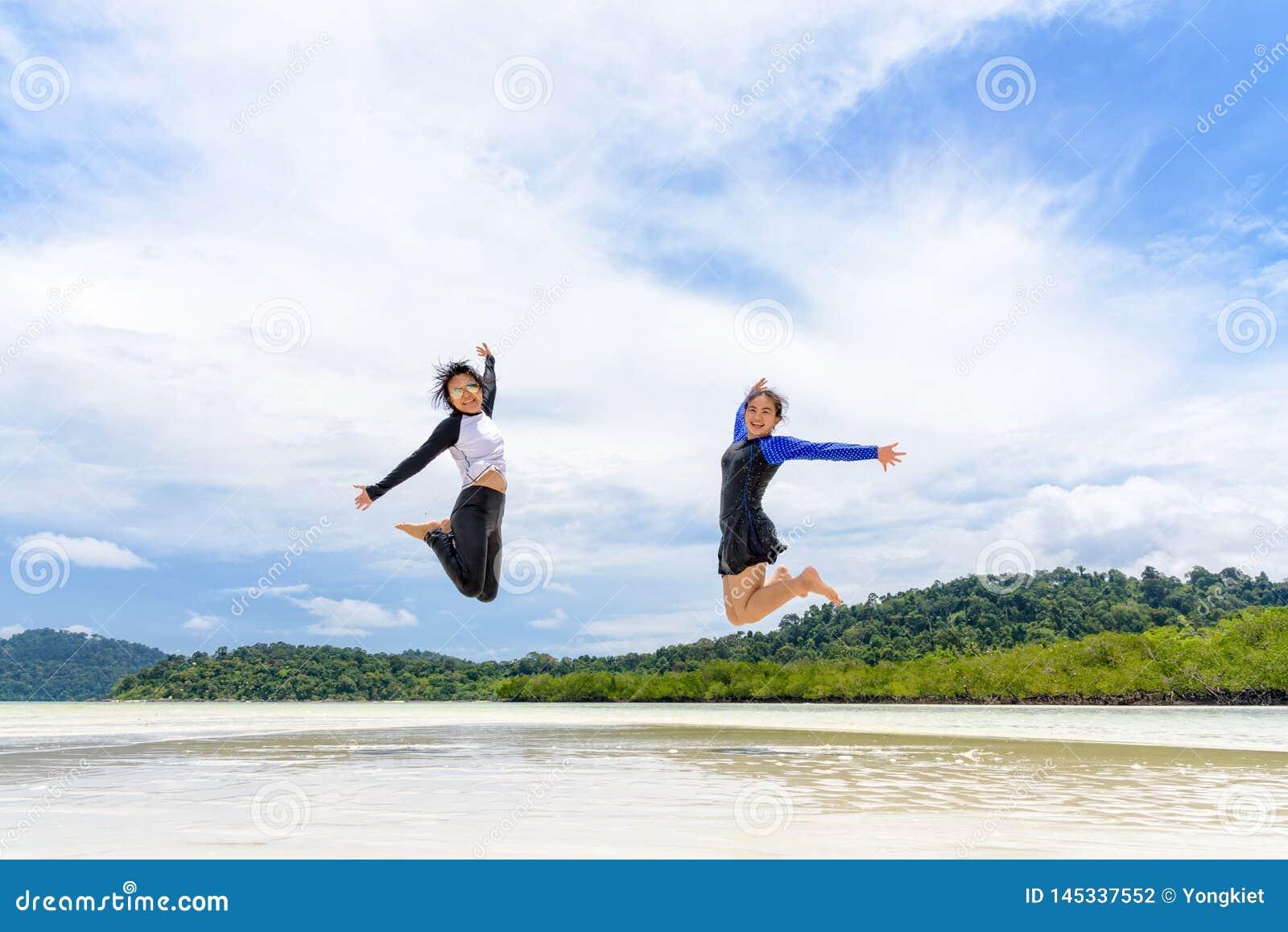 Dos amigos de muchachas adolescentes asiáticos que saltan para gozar en la playa
