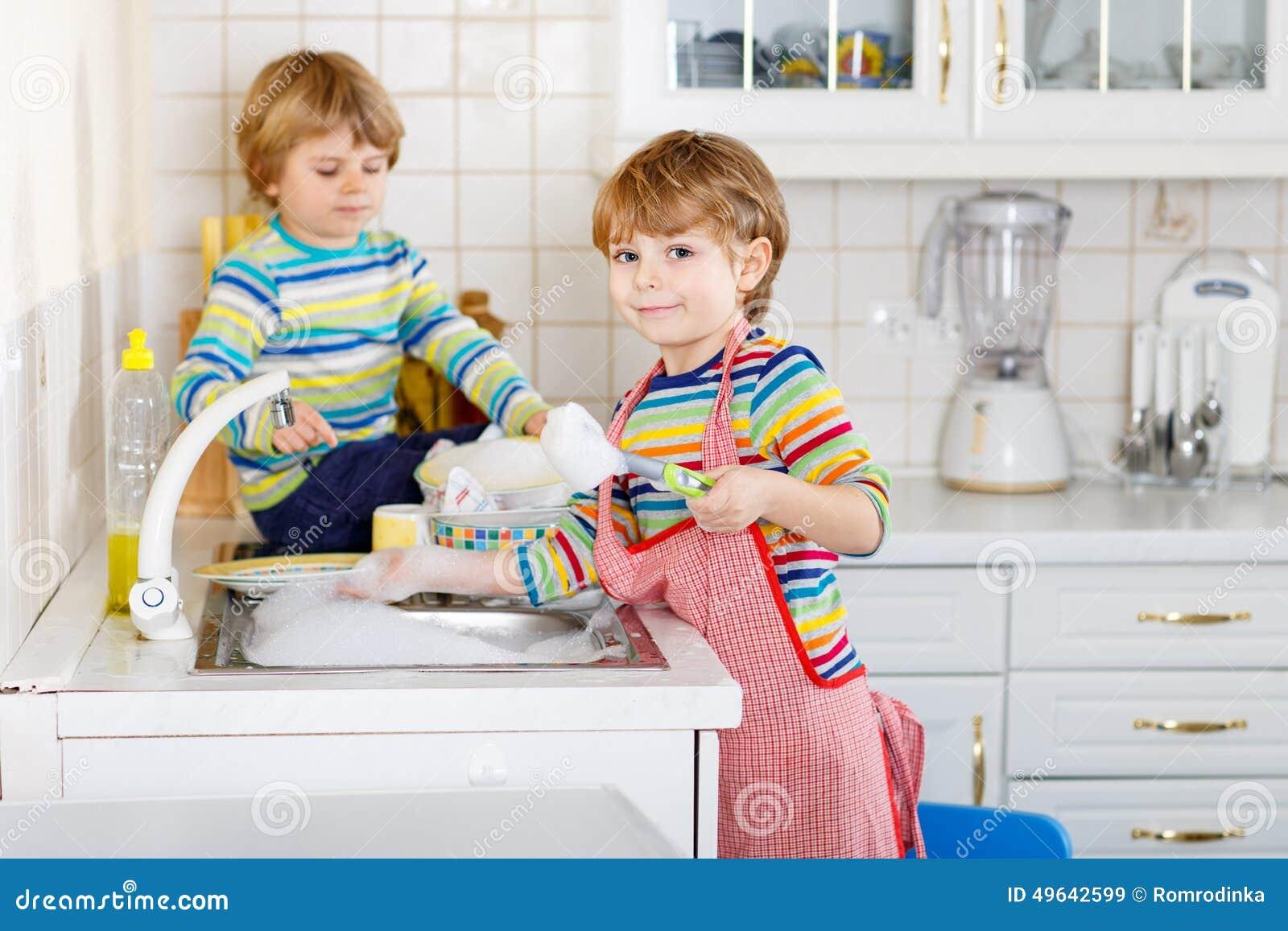 Dos amigos divertidos del ni o peque o que lavan platos en - Foto nino pequeno ...