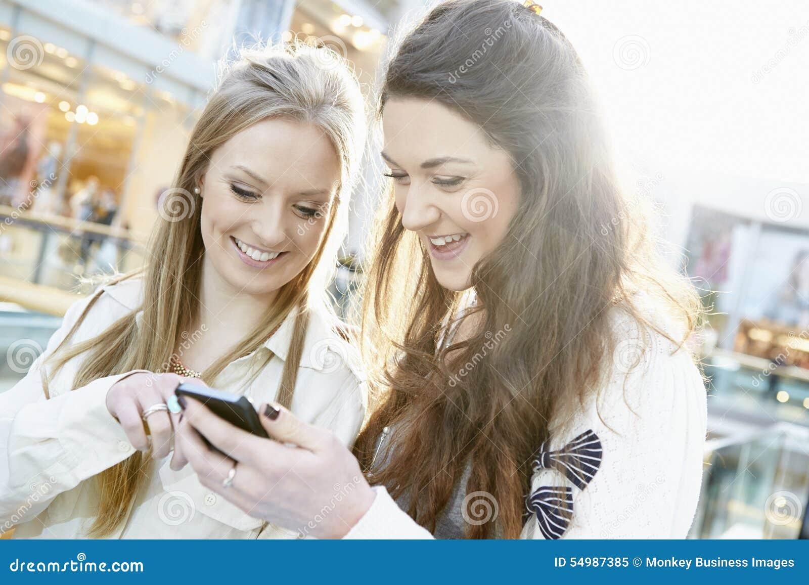 Dos amigos femeninos que hacen compras en la alameda que mira el teléfono móvil