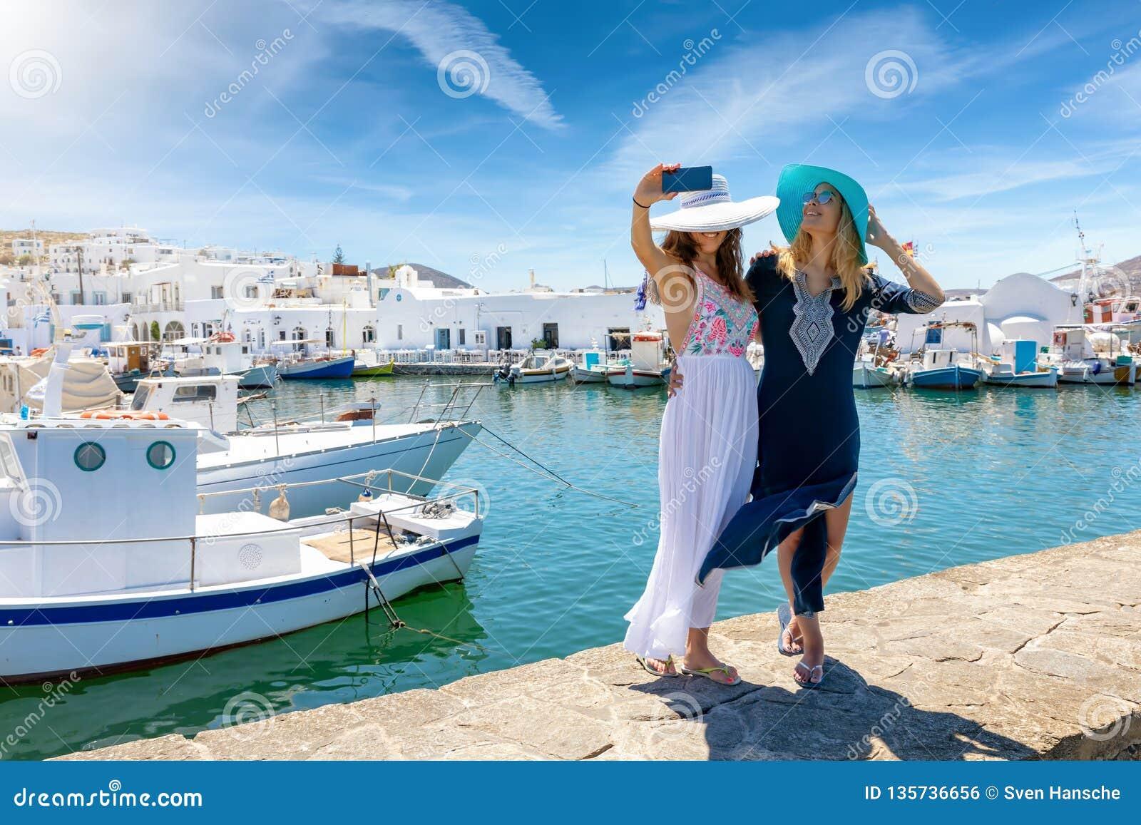 Dos amigos femeninos que toman las fotos del selfie en el pueblo pesquero Naousa