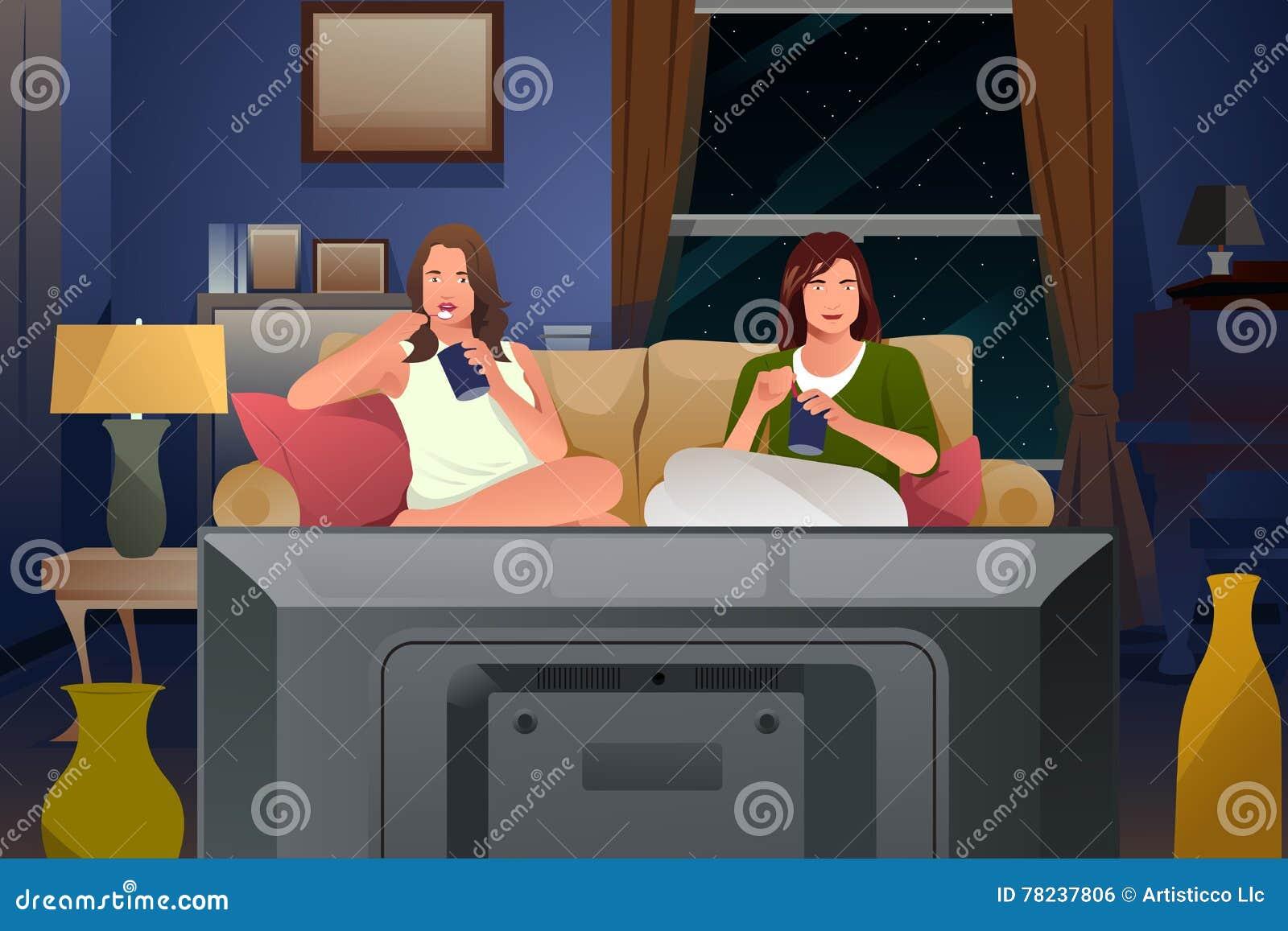 Dos amigos femeninos que ven la TV y que comen el helado