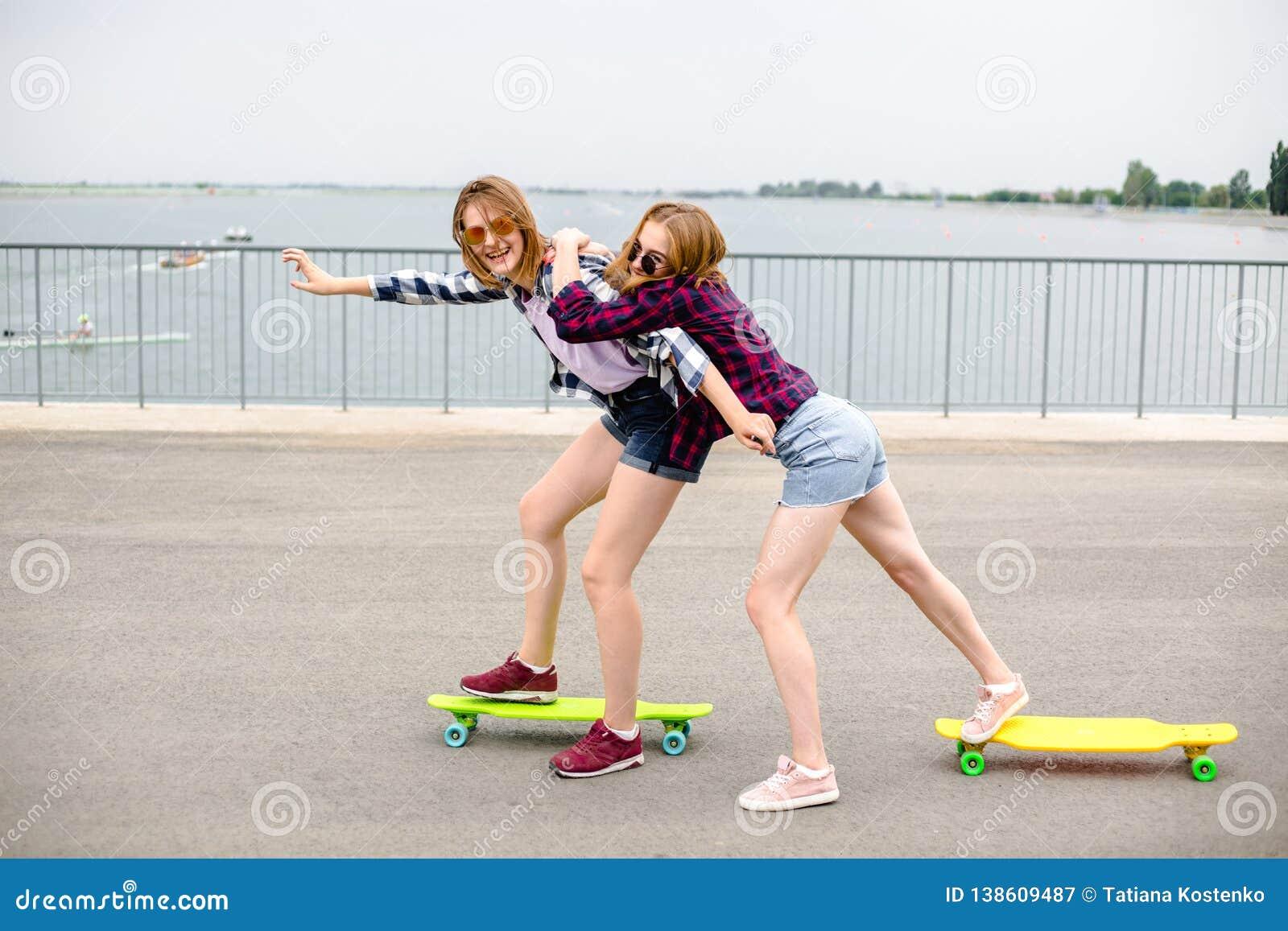 Dos amigos femeninos sonrientes que aprenden longboard que monta con la ayuda Concepto de la amistad