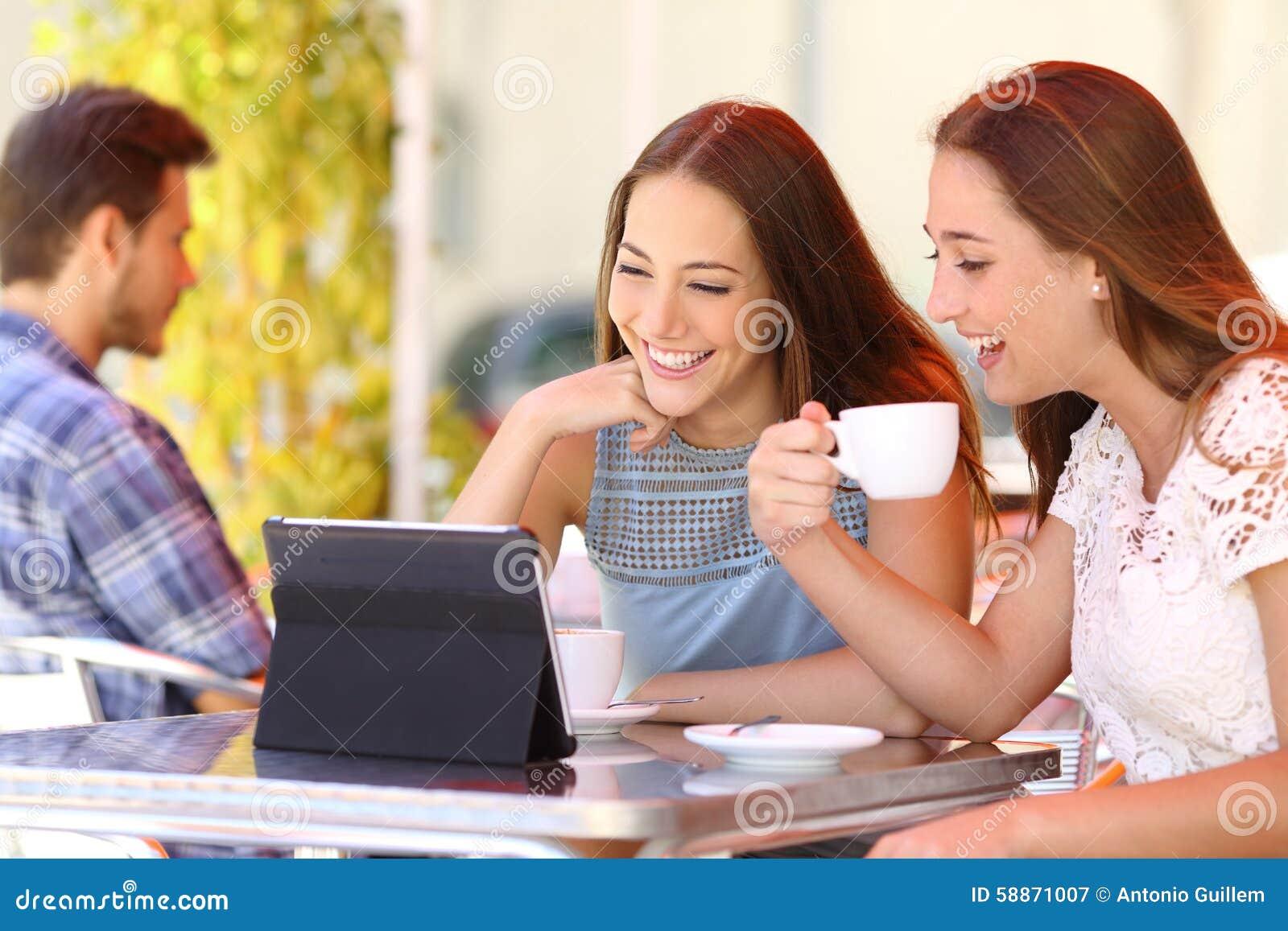 Dos amigos o hermanas que miran los vídeos en una tableta