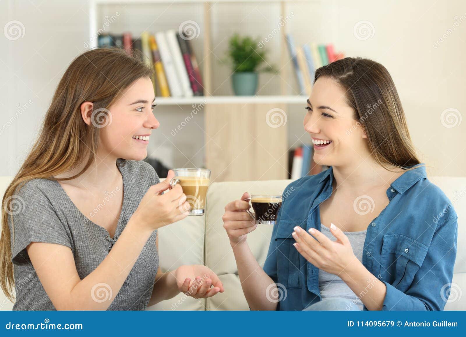 Dos amigos que hablan y que beben el café en casa