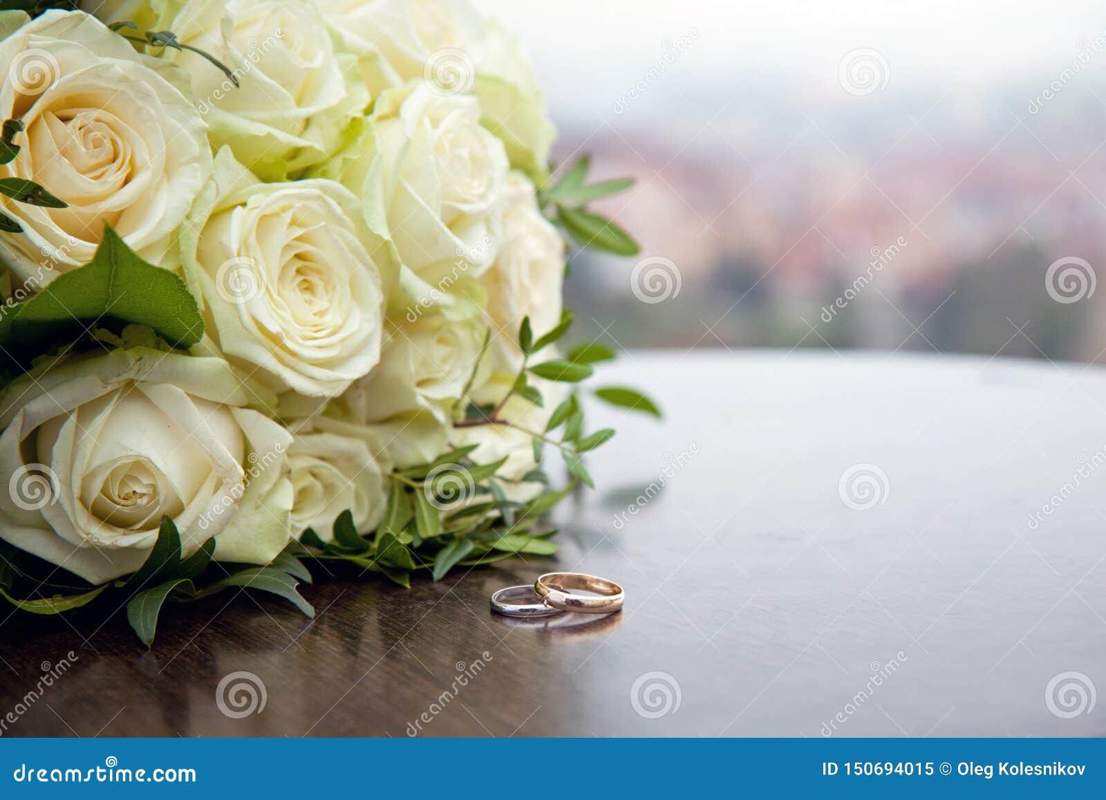 Dos anillos de bodas del oro en una tabla de madera redonda
