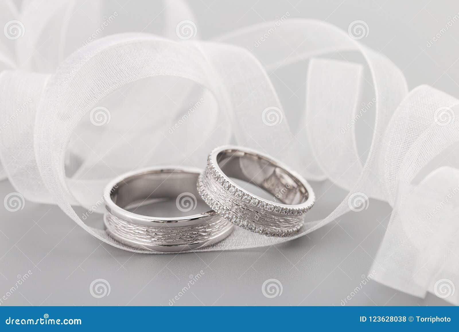 2c9a81ad598c Dos anillos de la bodas de plata con los diamantes en fondo gris Anillos de  oro blanco con las gemas Concepto de la invitación de la boda con el sobre