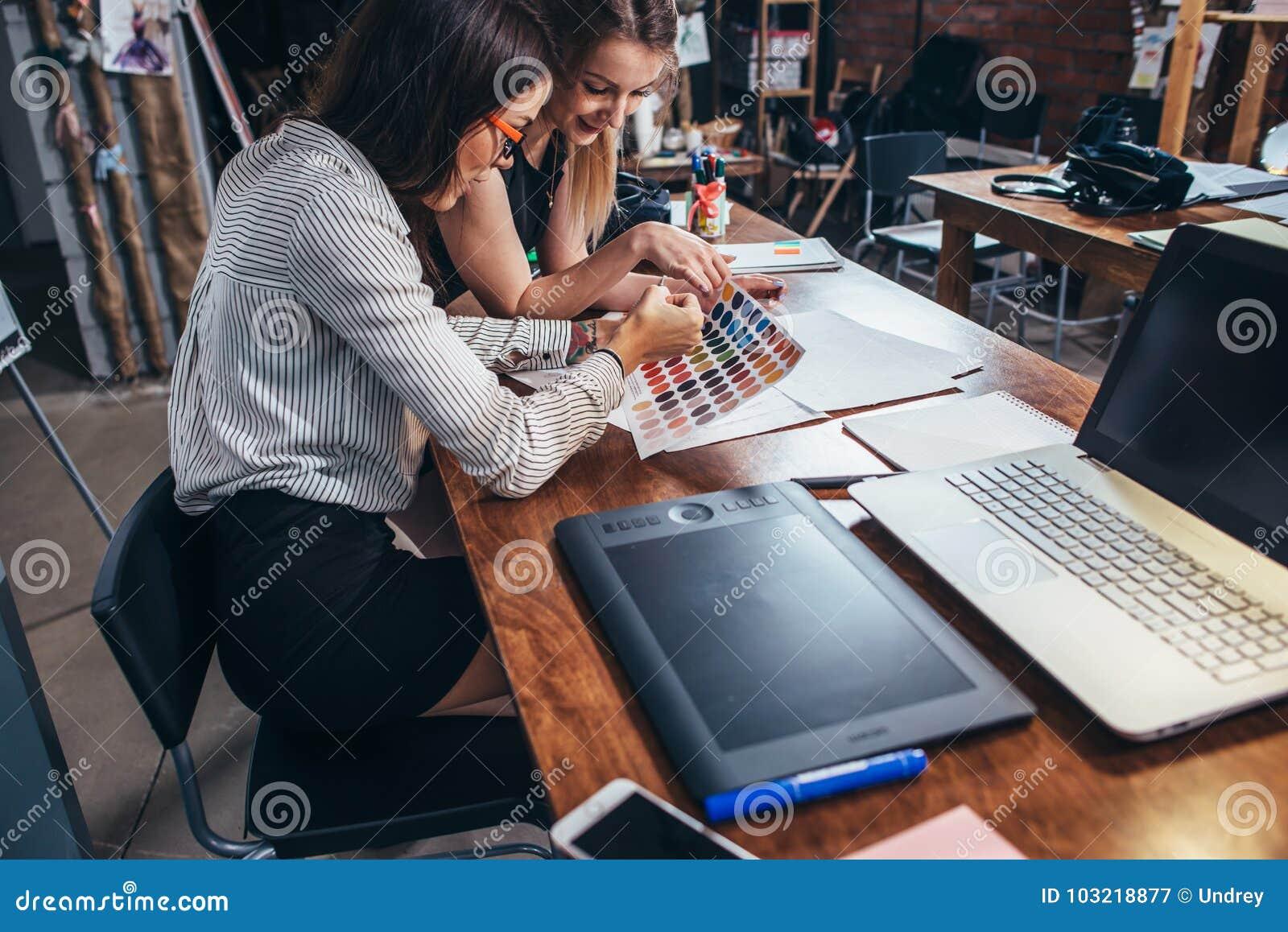 Dos arquitectos de sexo femenino que trabajan junto usando las muestras del color que se sientan en el escritorio con el ordenado