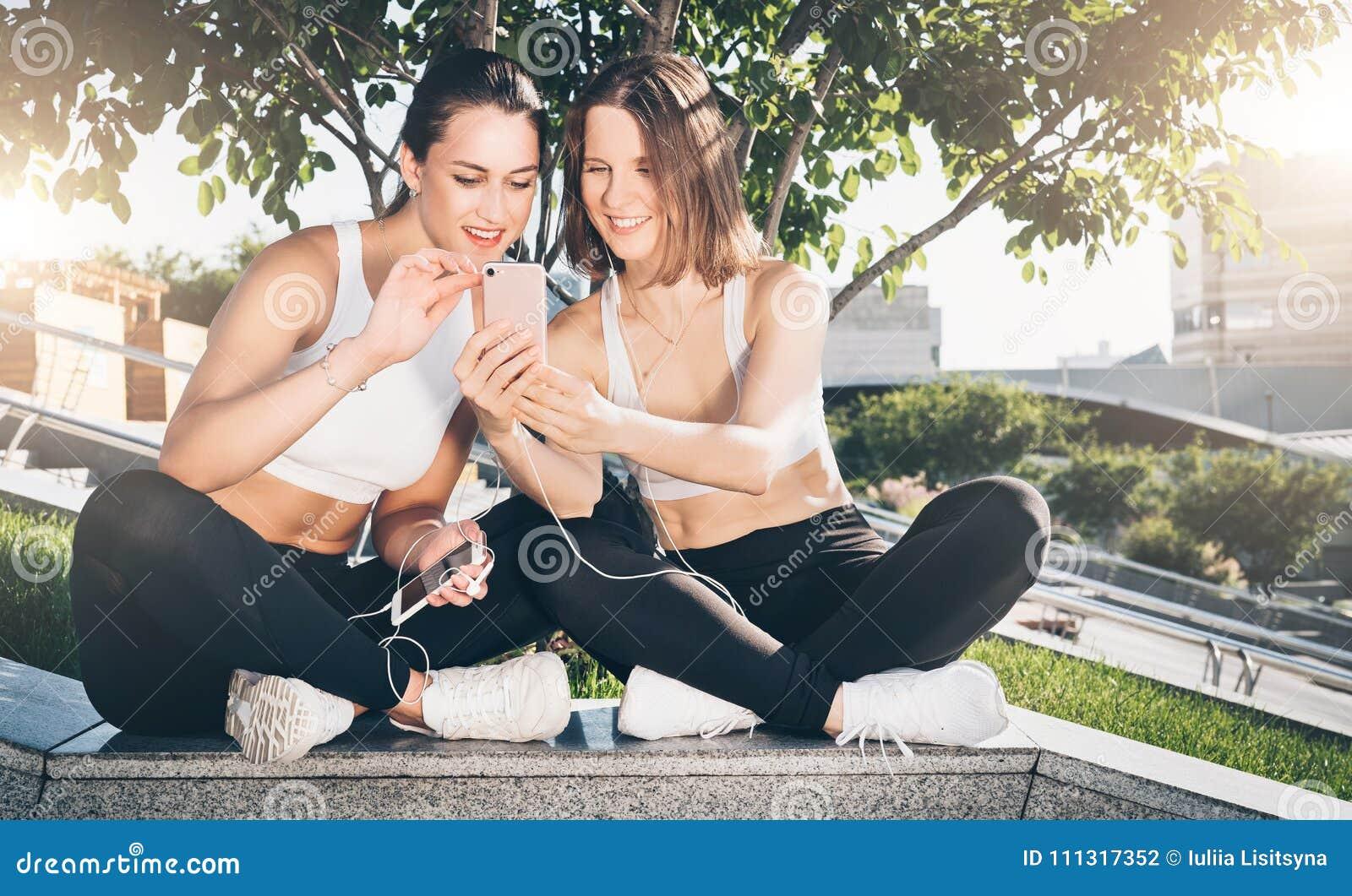 Dos atletas de las mujeres jovenes en ropa de deportes se están sentando en parque, se relajan después de deportes entrenando, ut