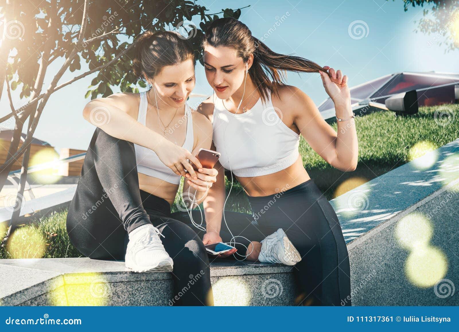 Dos atletas en la ropa de deportes que se sienta en parque, se relajan después de deportes entrenando, smartphone de las mujeres