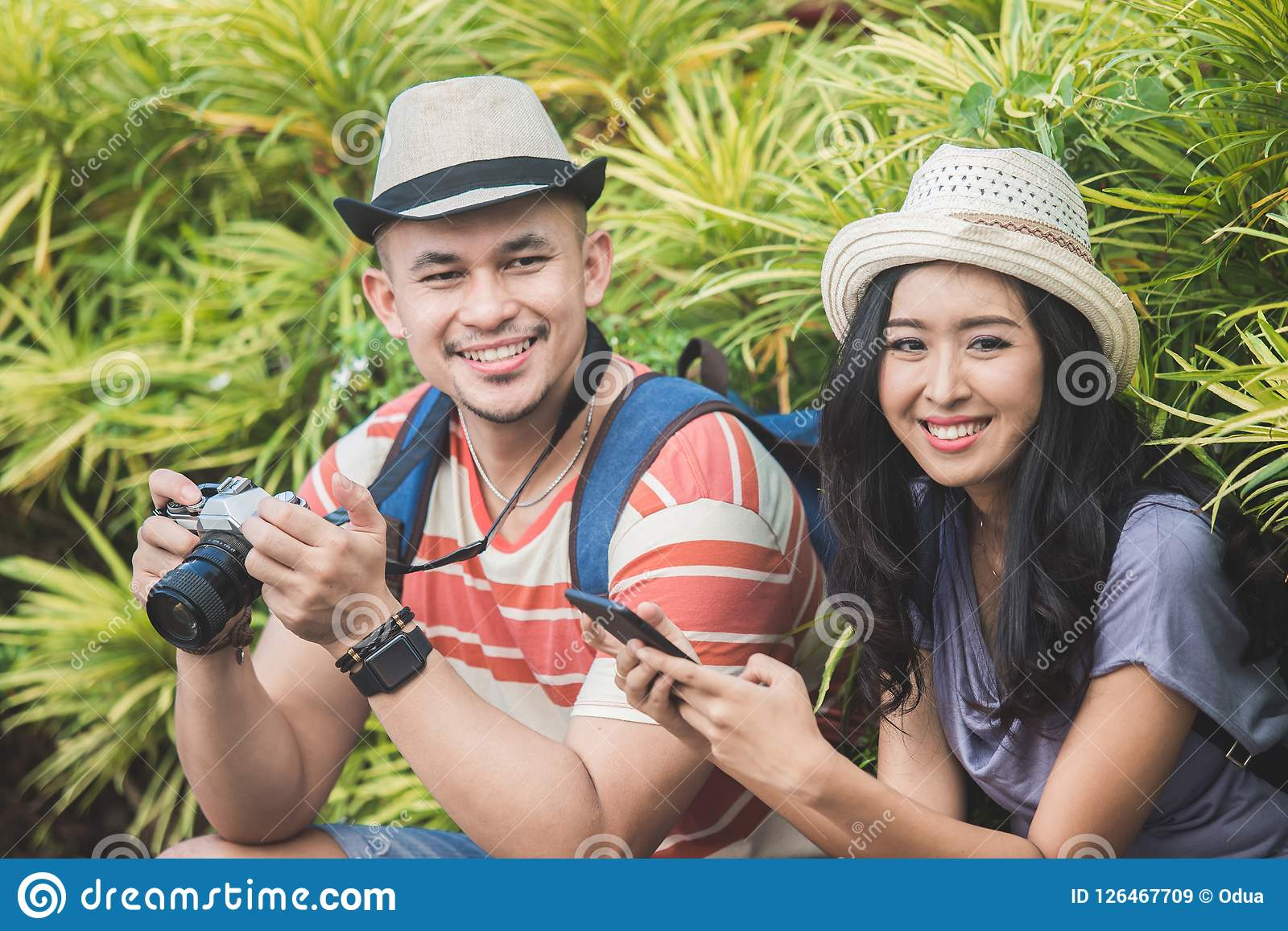 Dos backpackers con el sombrero del verano que sonríen a la cámara