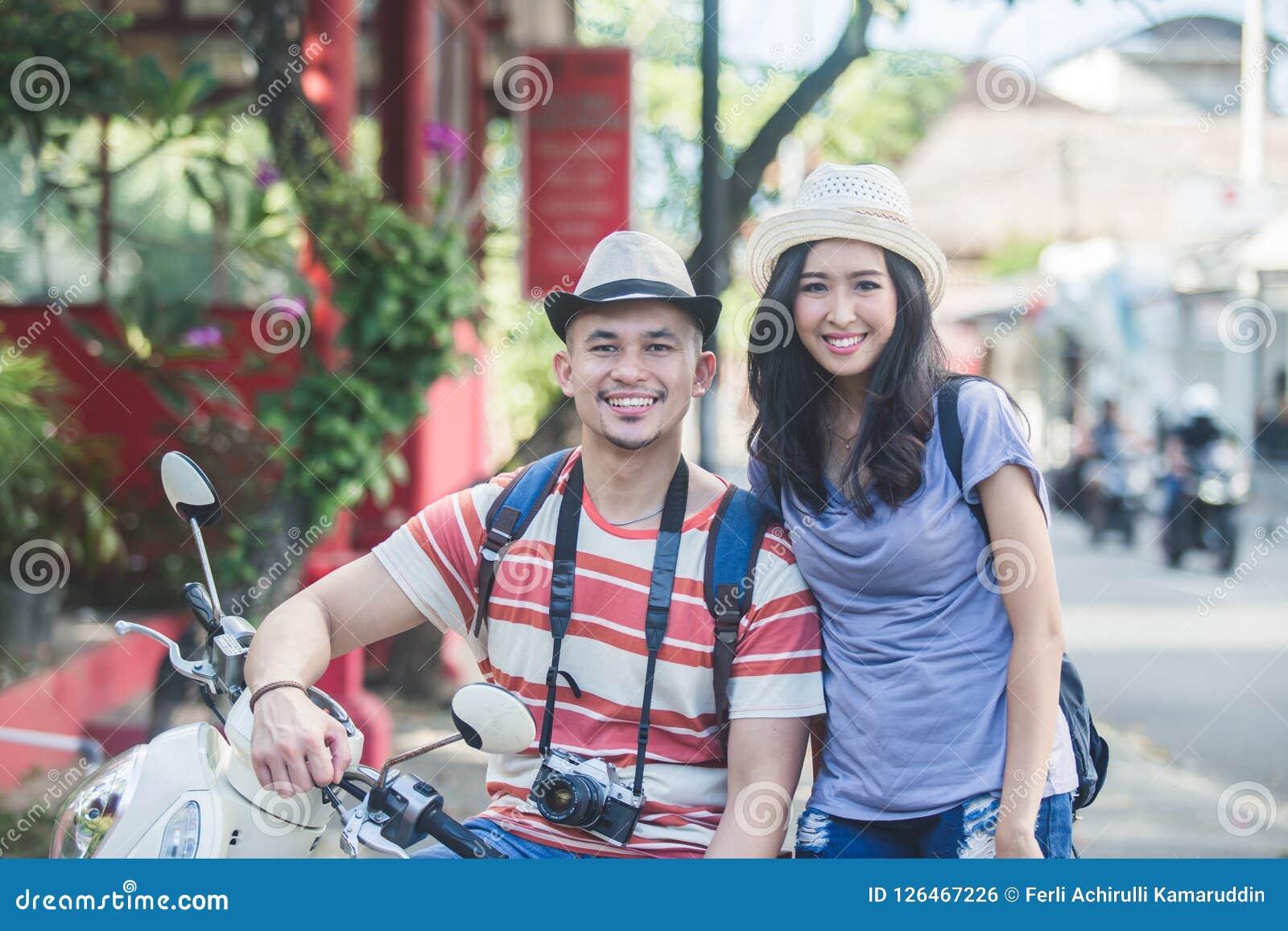 Dos backpackers con el sombrero del verano que sonríen a la cámara mientras que se sienta