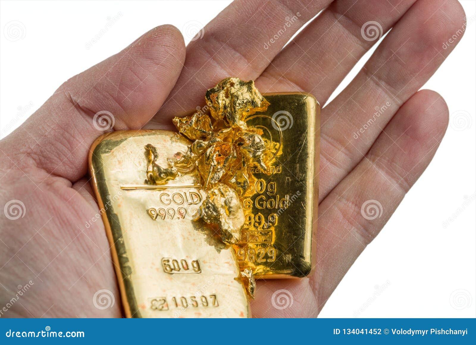 Dos barras de oro y varias pepitas de oro en la palma