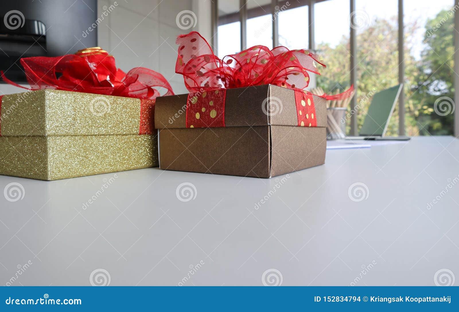 Dos boexes del regalo en el escritorio de trabajo blanco en la oficina