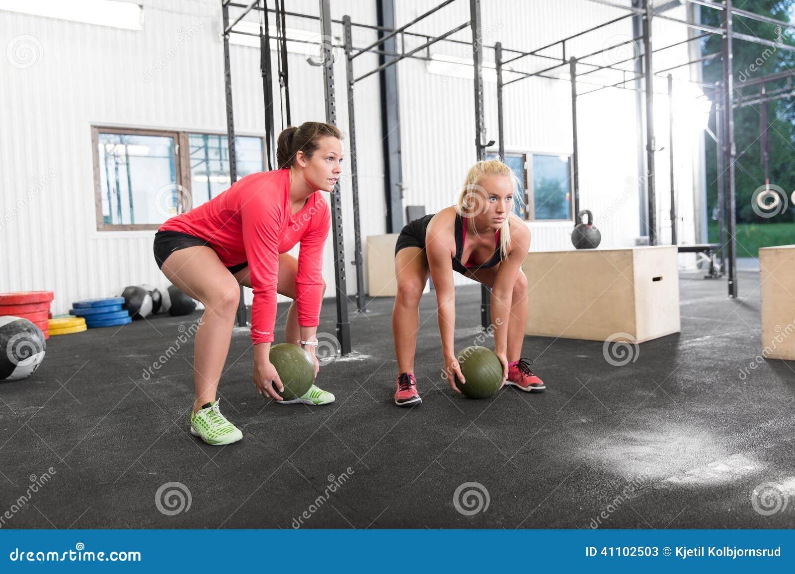 Dos bolas del golpe del crossfit de las elevaciones de las mujeres