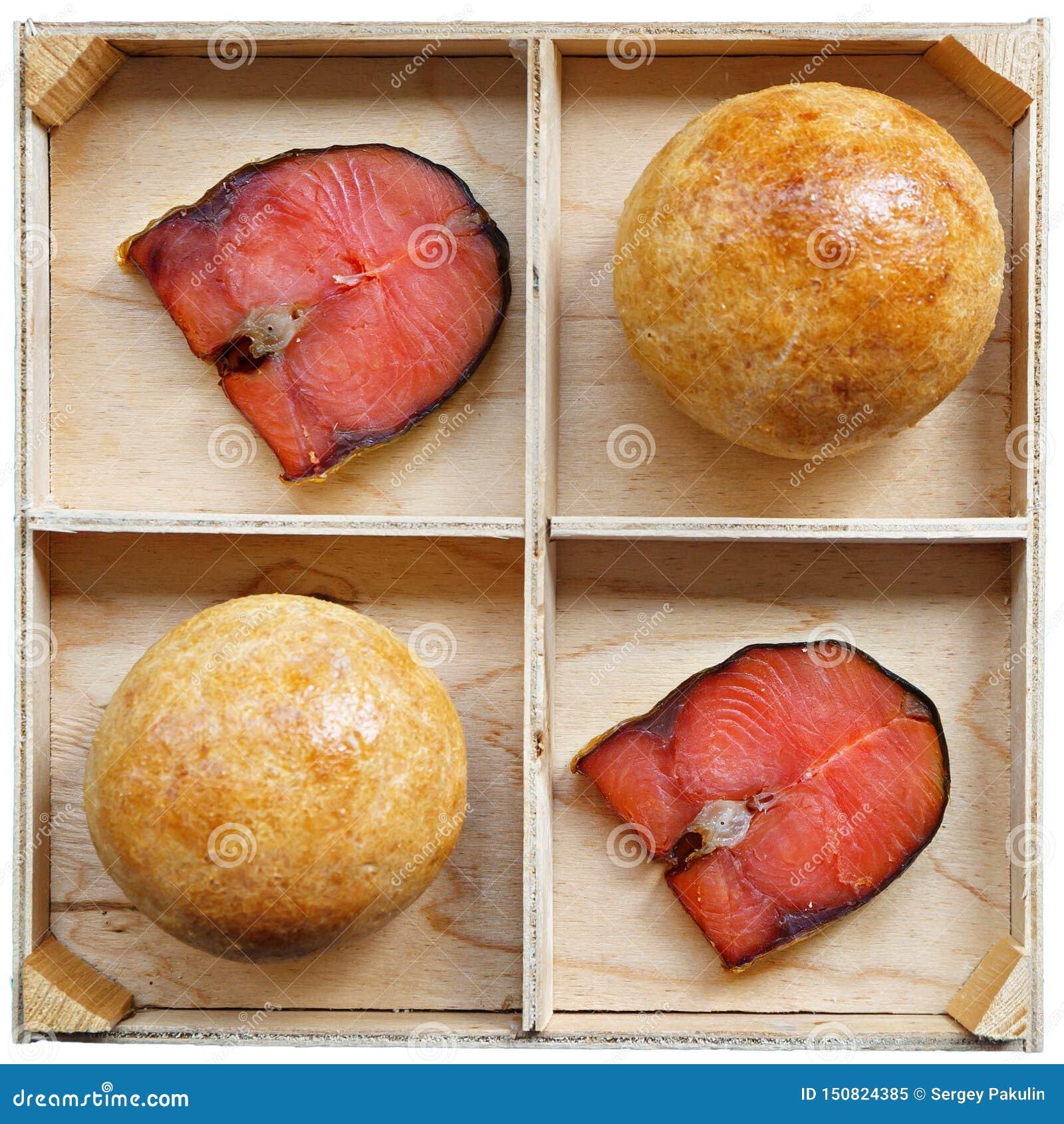 Dos bollos del bocadillo y 2 pedazos de mentira roja de los pescados en un soporte de madera Ingredientes alimentarios sanos Foto