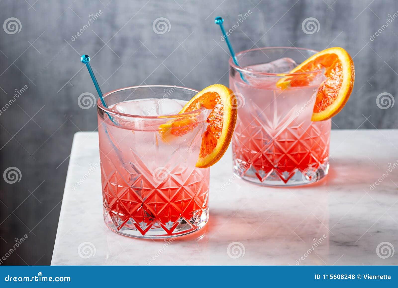Dos cócteles de la ginebra y del tónico de la naranja de sangre en contador