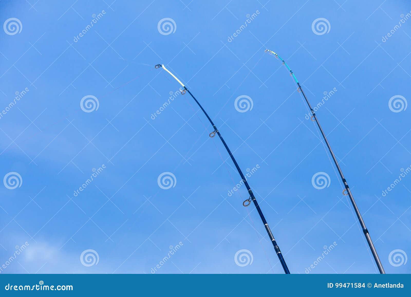 Dos cañas de pescar con el cielo azul en fondo