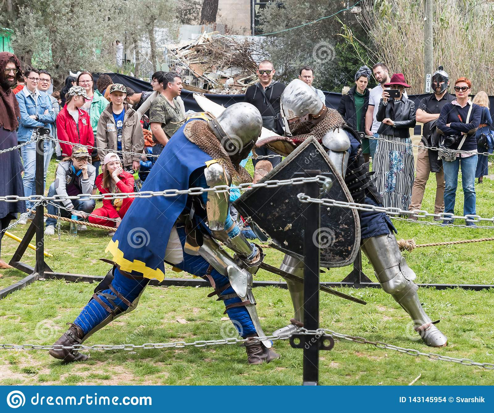 Dos caballeros con los escudos y las espadas luchan en el anillo en el festival de Purim con rey Arthur en la ciudad de Jerusalén