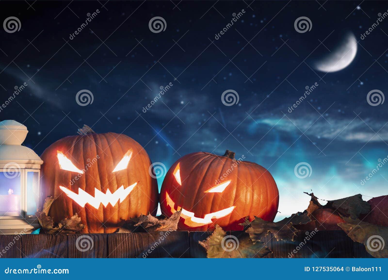 Dos calabazas de Halloween en la cerca con el cielo estrellado