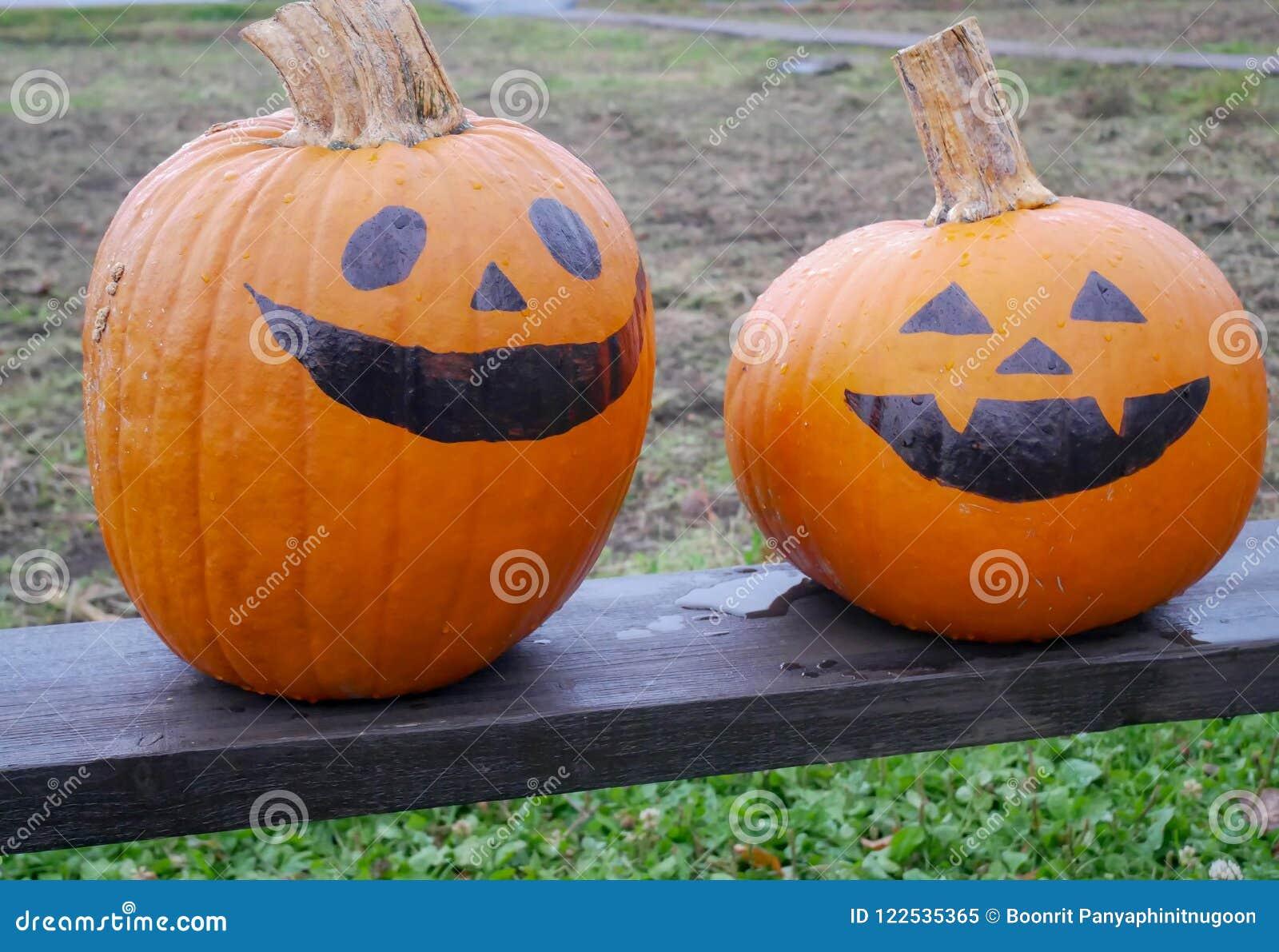 Dos calabazas pintadas como halloween hacen frente colocado en la tabla de madera en una granja - Calabazas de halloween pintadas ...