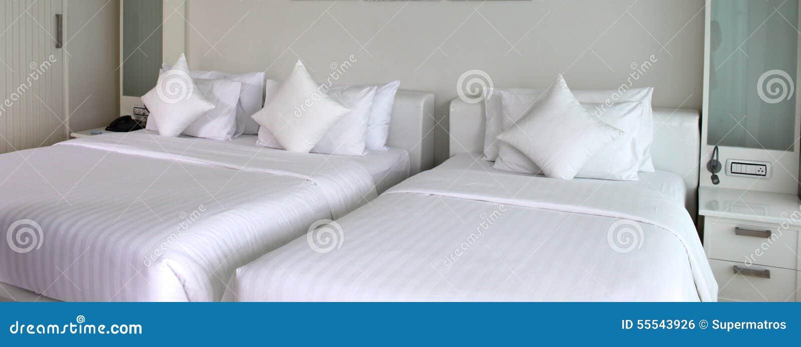 Dos camas con las colchas y las almohadas blancas foto de - Almohadas para cama ...