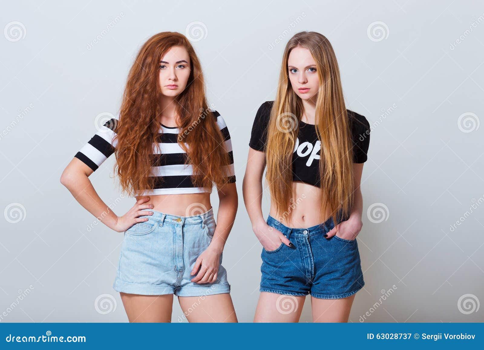 dos chicas jvenes atractivas hermosas en pantalones cortos de los vaqueros encendido fotografa de archivo libre