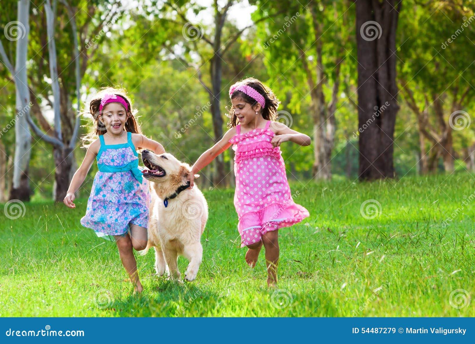 Dos chicas jóvenes que corren con un golden retriever en la hierba