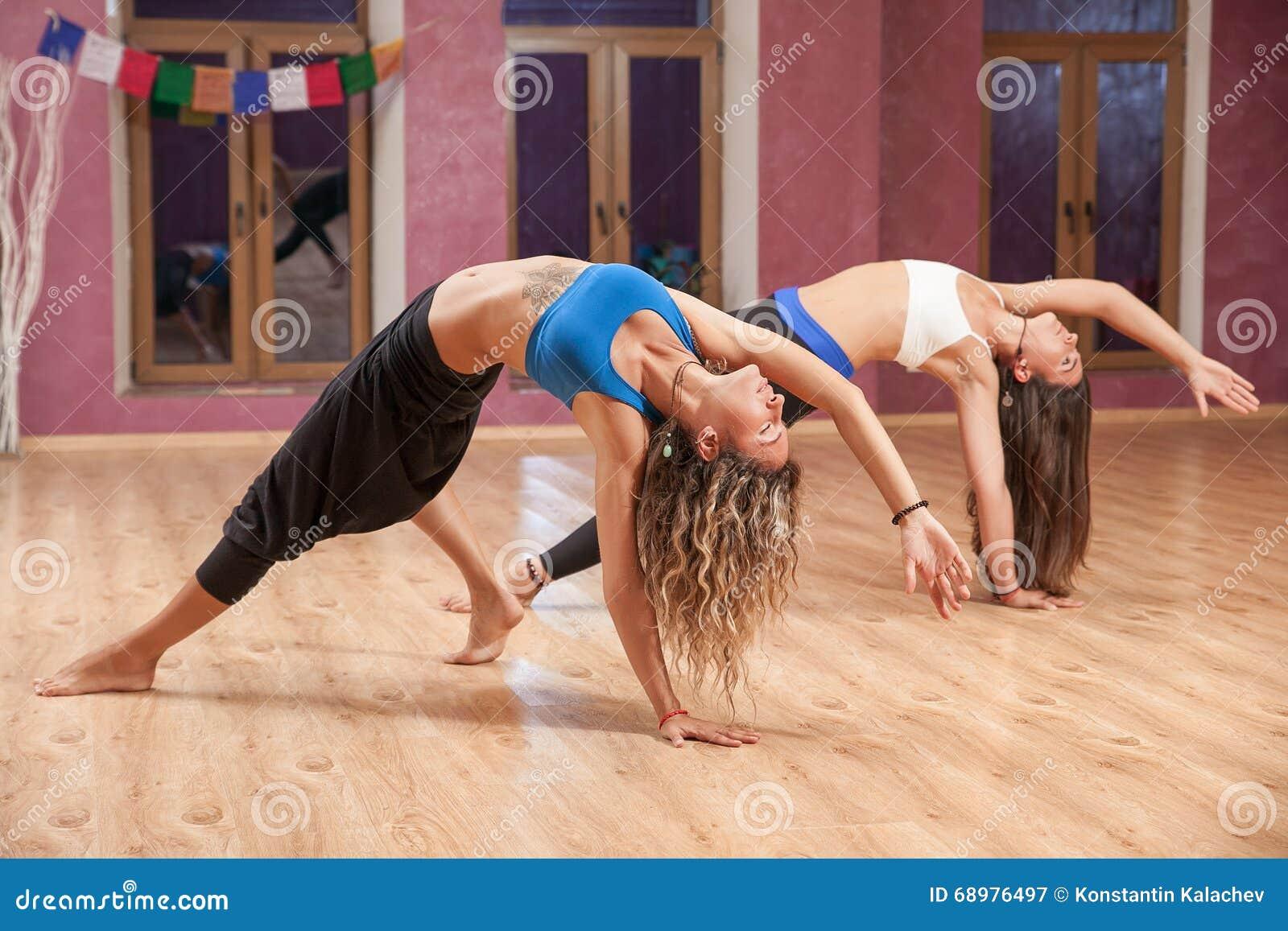 Dos chicas jóvenes que hacen yoga dentro