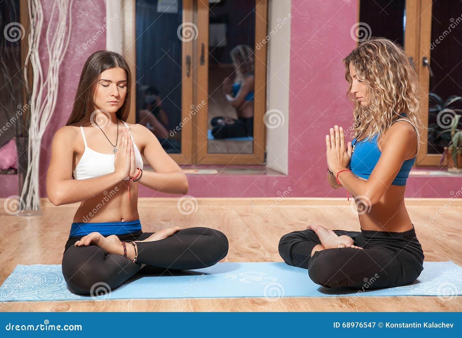 Dos chicas jóvenes que hacen yoga en la estera dentro
