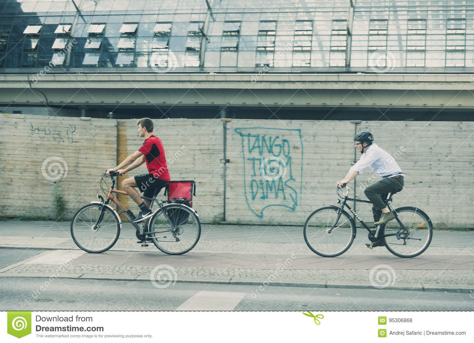 Dos ciclistas en el ambiente urbano, el rojo que lleva, el otro en traje de la indumentaria de oficina informal y la camisa, esta