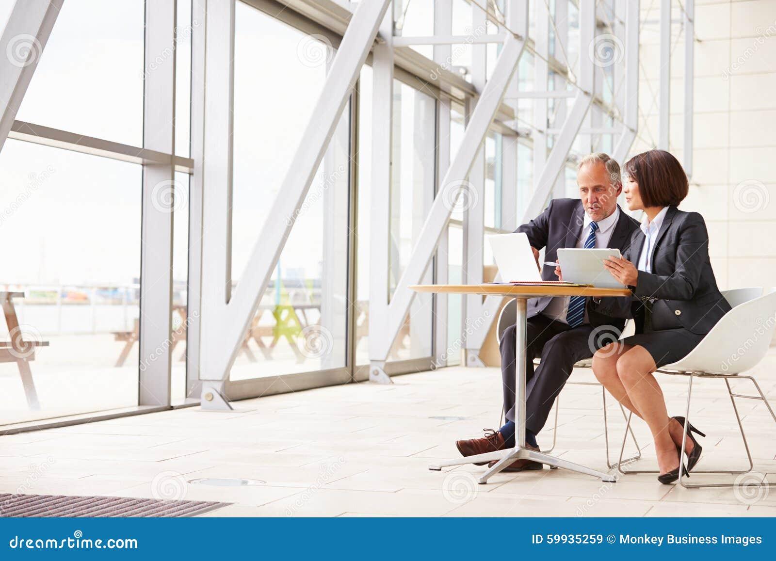 Dos colegas mayores del negocio en la reunión en interior moderno