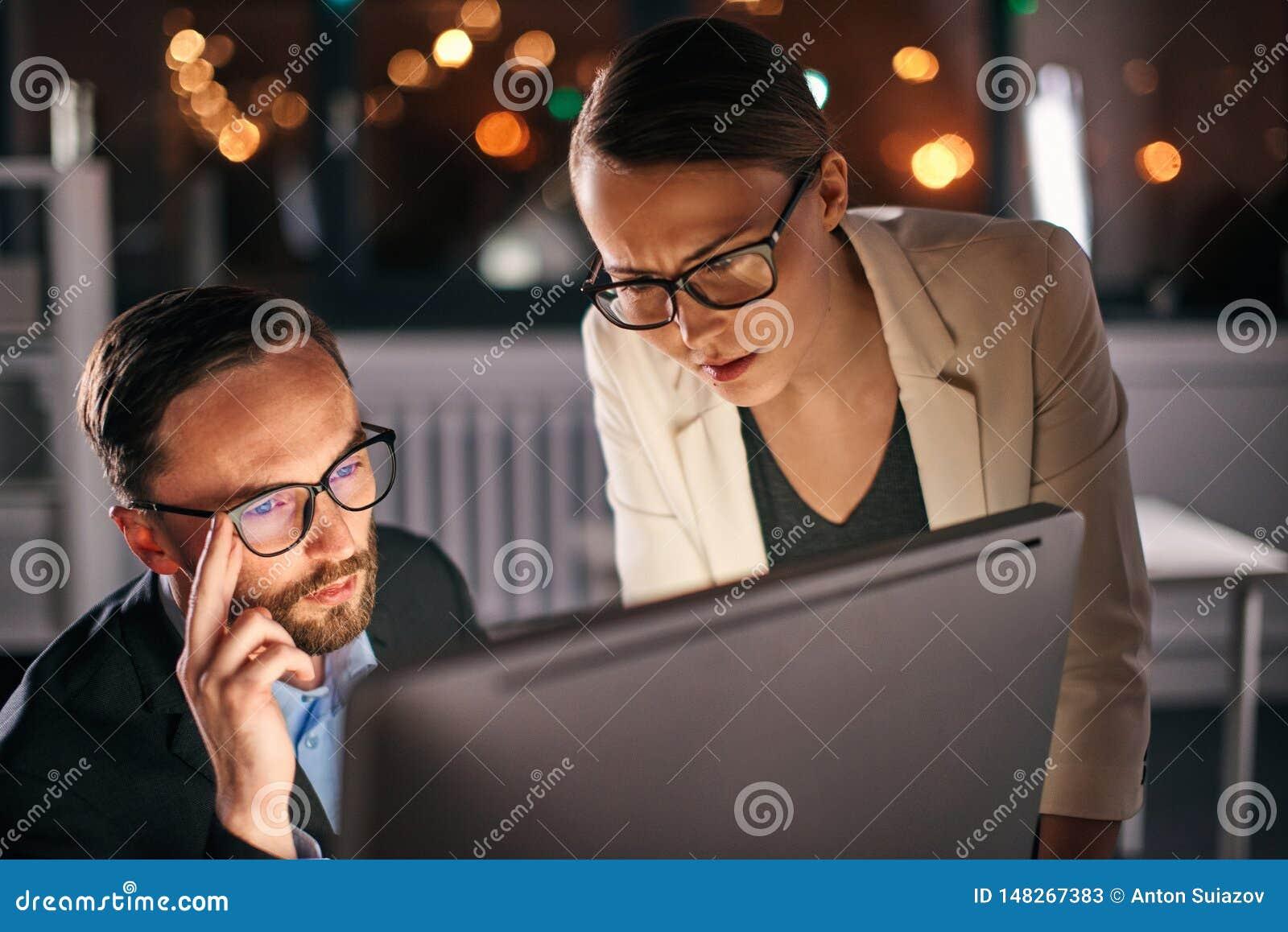 Dos colegas que trabajan en el ordenador en la noche