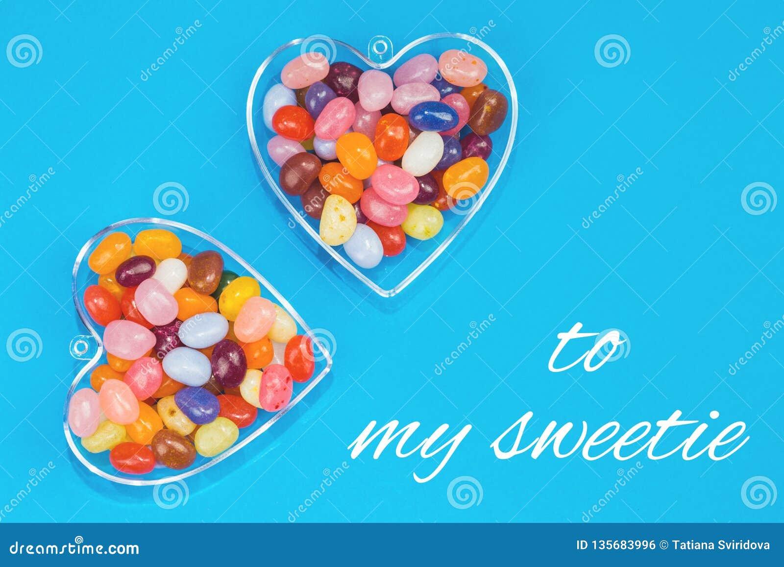 Dos corazones con los caramelos en fondo azul