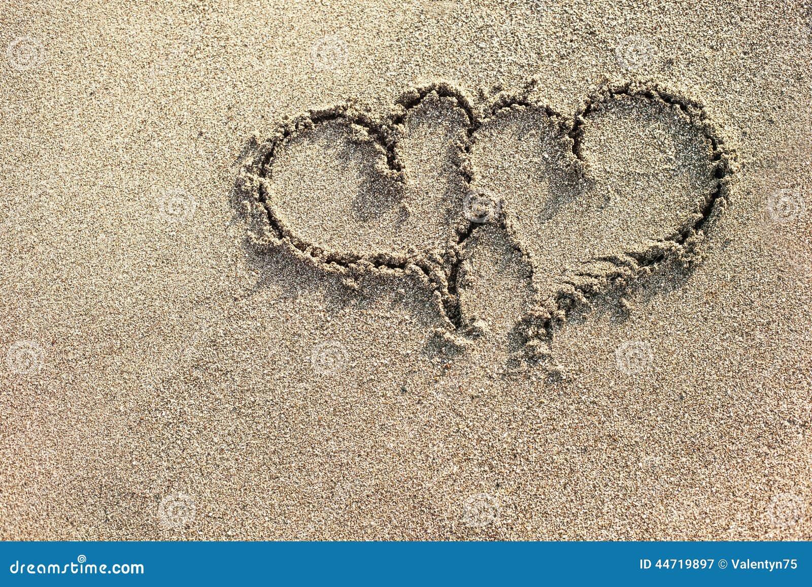 Amor Escrito En Arena: Dos Corazones Escritos En La Arena Imagen De Archivo
