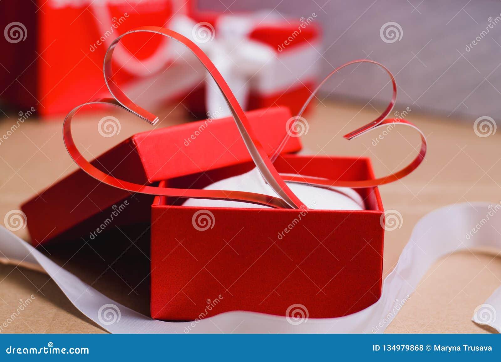 Dos corazones rojos de papel hechos en casa en una caja de regalo roja, símbolo del día de tarjeta del día de San Valentín