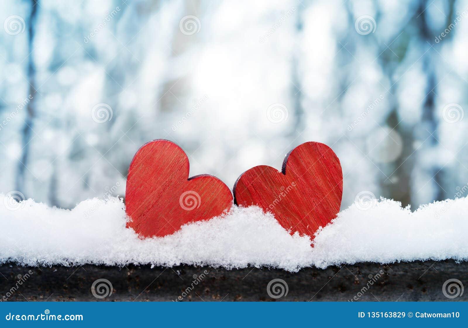 Dos corazones rojos del vintage romántico hermoso junto en un fondo blanco del invierno de la nieve Amor y concepto del día de ta