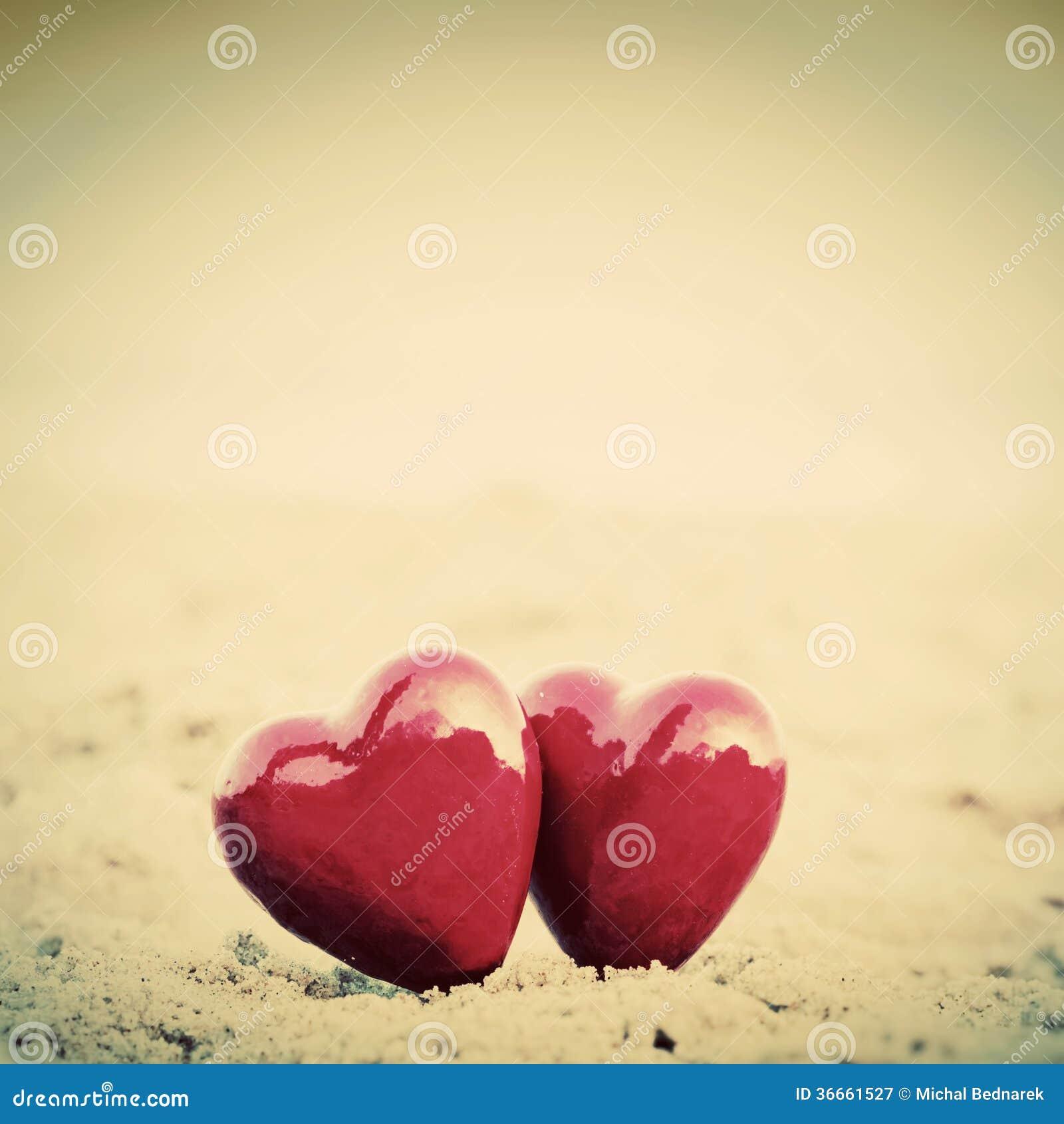 Dos corazones rojos en la playa que simboliza amor
