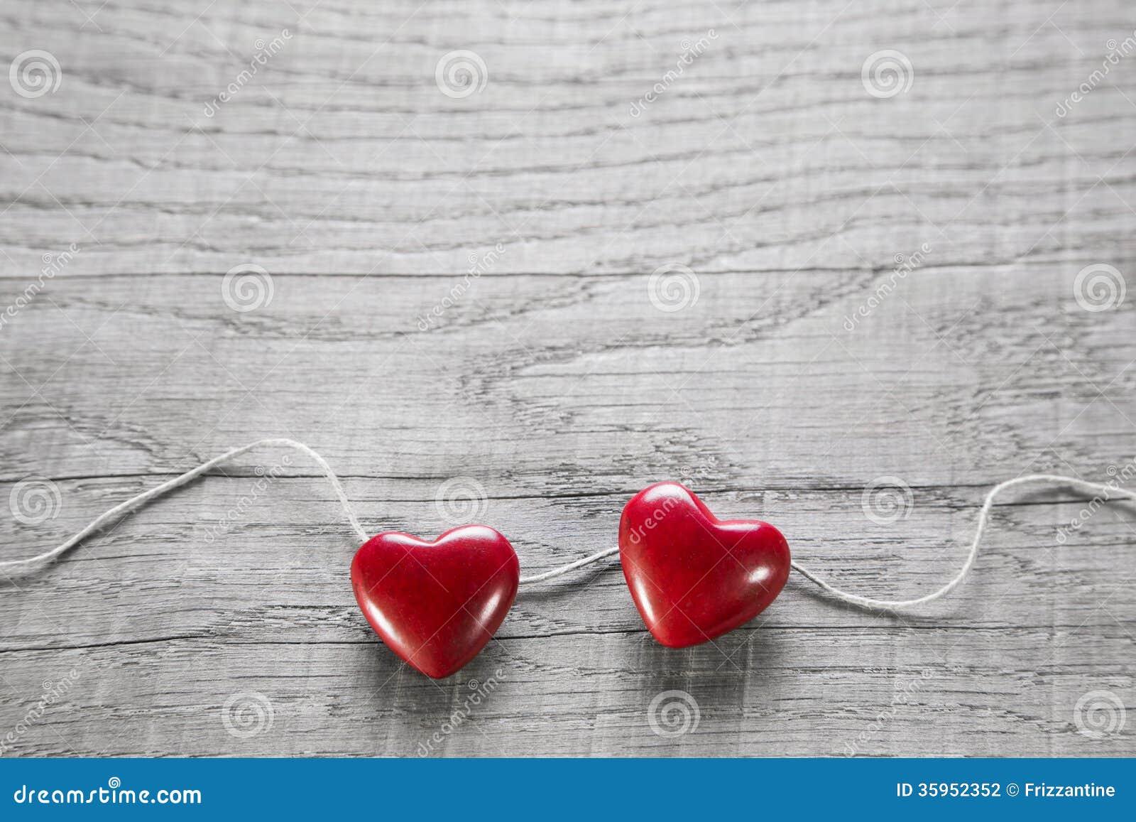 Dos corazones rojos en un fondo lamentable de madera para la tarjeta del día de San Valentín.