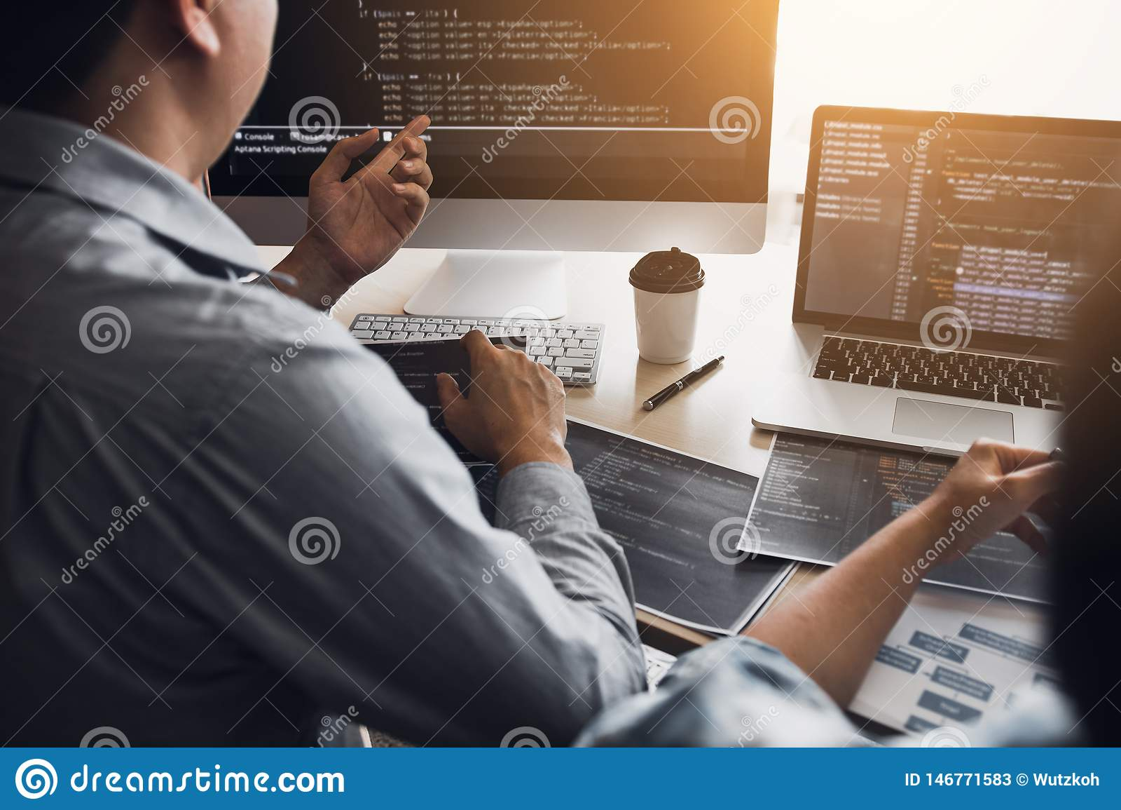 Dos desarrolladores de software están utilizando los ordenadores para trabajar así como su socio en el escritorio de oficina