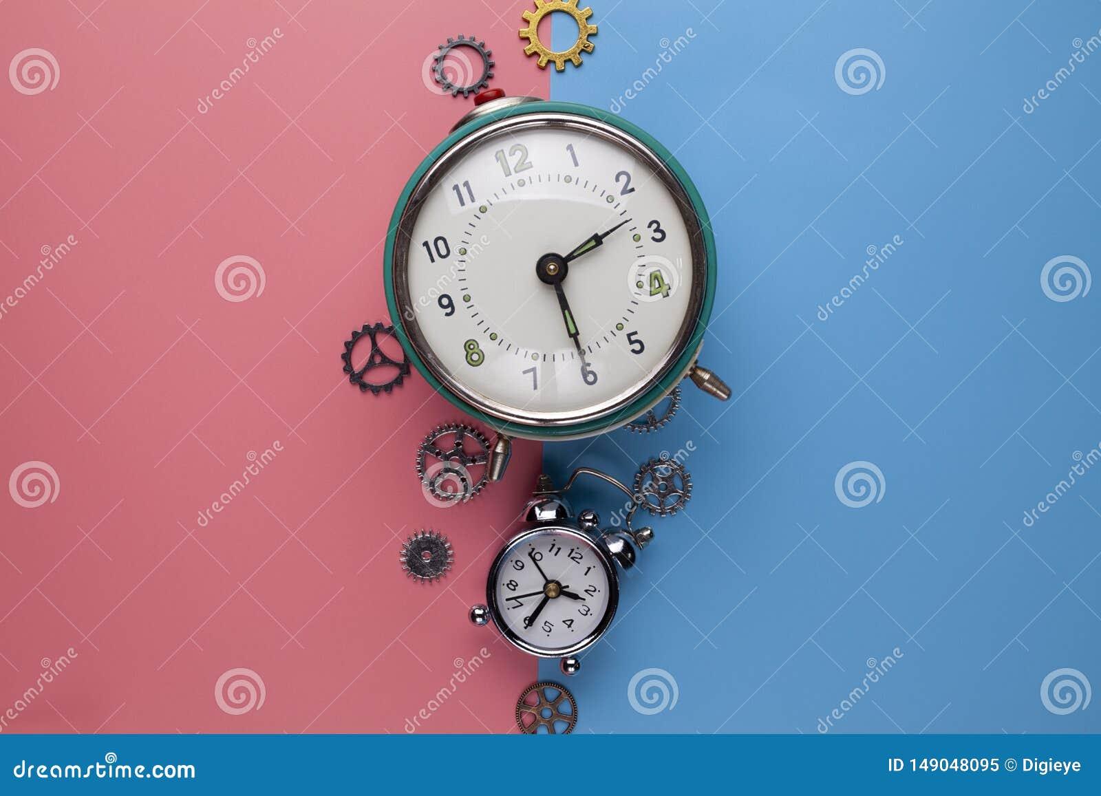 Dos despertadores viejos y pequeños engranajes, piezas del reloj en un fondo dos-coloreado