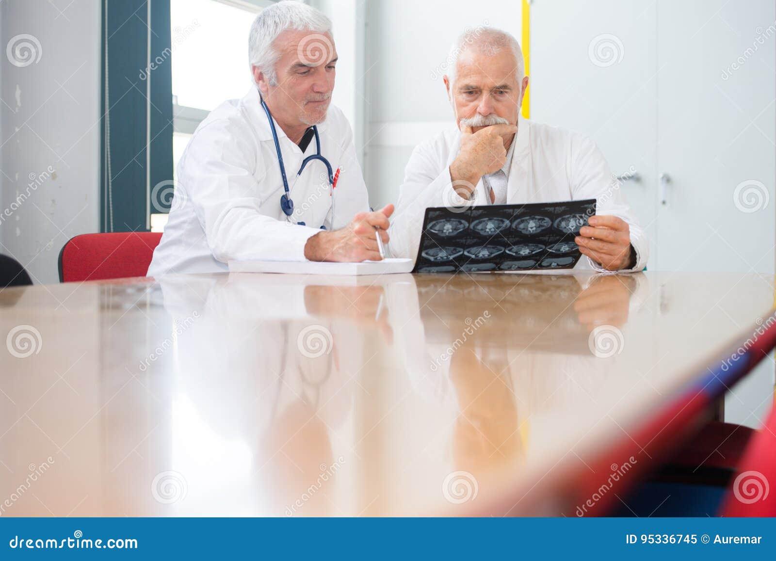 Dos doctores de sexo masculino que discuten radiografías en la tabla