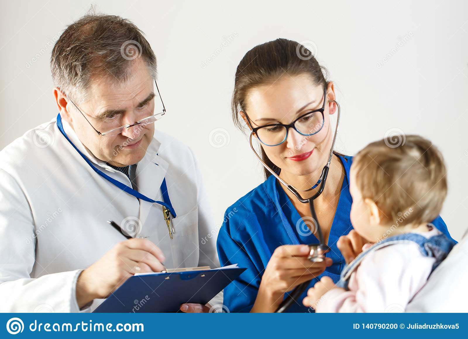Dos doctores examinan un pequeño niño, uno usando un estetoscopio y el otro que toma notas sobre una tarjeta