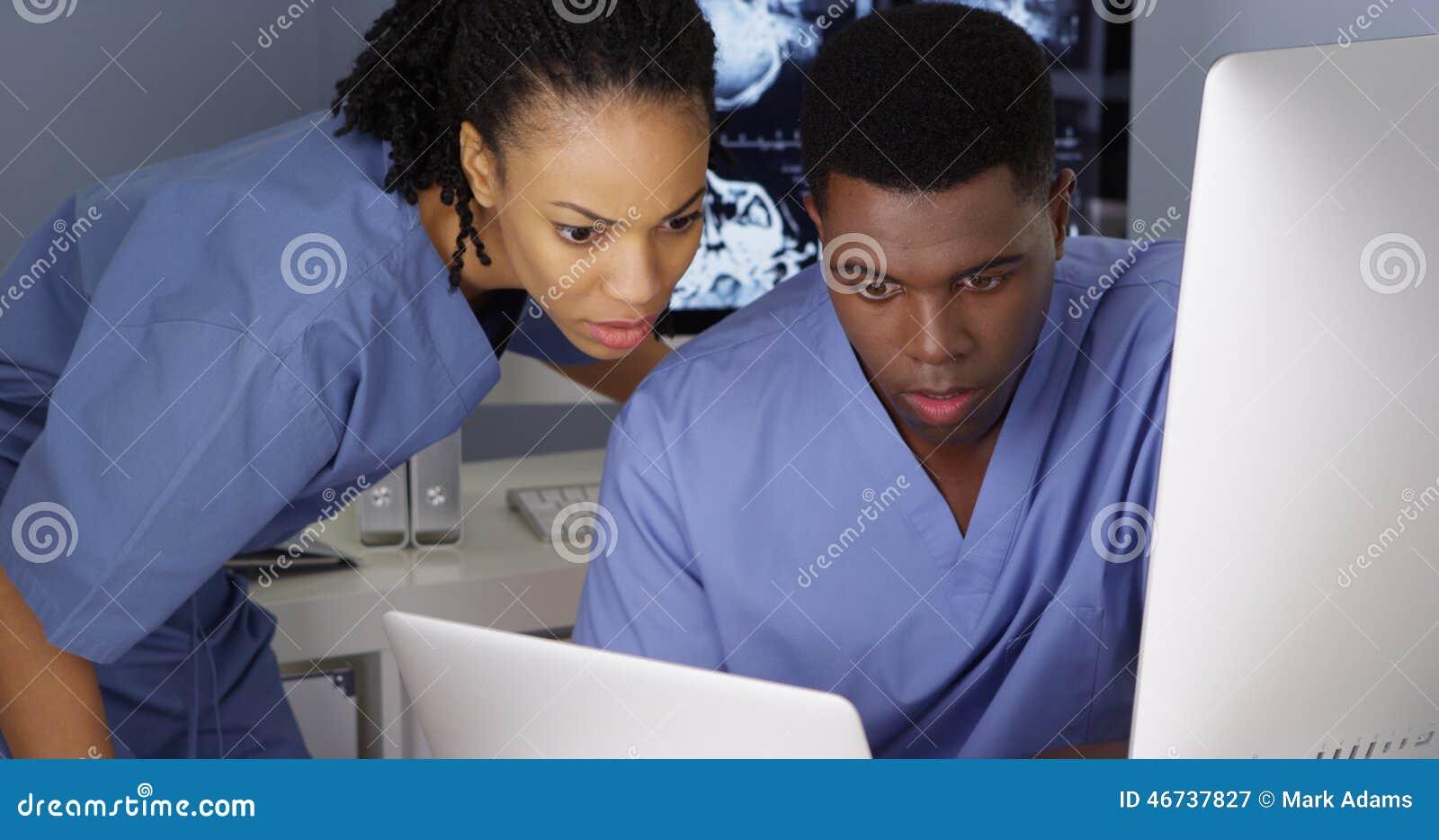 Dos doctores jovenes que trabajan junto en los ordenadores múltiples