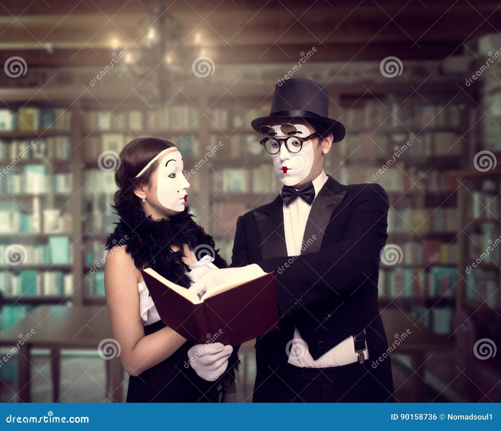 Dos ejecutantes del teatro de la pantomima que presentan con el libro