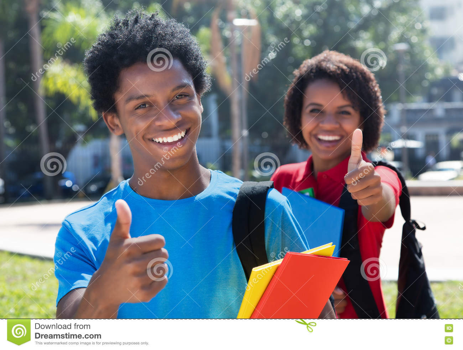 Dos estudiantes afroamericanos felices en el campus que muestra los pulgares